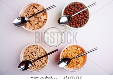Various corn flakes in different plates, four plates with flakes and spoons in the middle stands a glass of milk, pads, chocolate balls, circles, and flakes, isolated on white background,