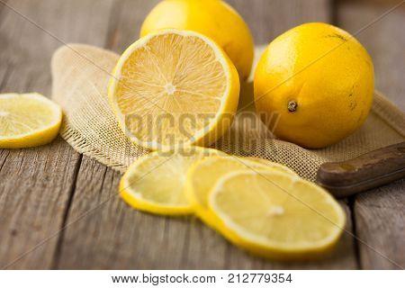 Half of lemon on a wooden board. Lemons on a wooden background. Lemons. Fruits. Lemon halves. Mint. Healthy food concept. Copyspace