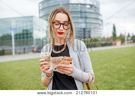 Portrait of a young and sad businesswoman counting money standing in front of the European parliament building in Strasbourg, France
