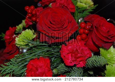 Red and green winter holiday flower arrangement with silver ornaments and red holly berries.