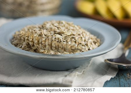 Oat flakes or oatmeal in ceramic bawl on blue table. Prepare oat flakes for bakery or cooking.Natural organic food in vintage style concept.Oat flake, oatmeal background and texture.