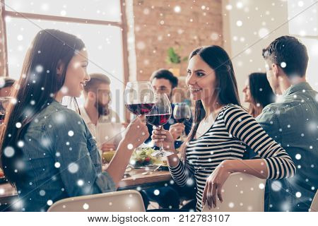 Close Up Of Two Girls Cliking Glasses Of Wine At The Party. They Are Happy And Enjoy The Celebration