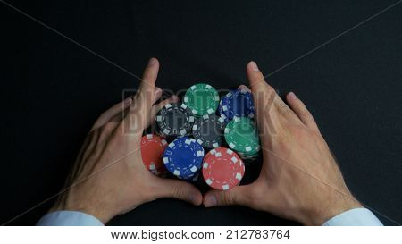 Stack of poker chips and two hands on table. Closeup of poker chips in stacks on green felt card table surface. Poker chips and hands above it on green table. Dealer 4K