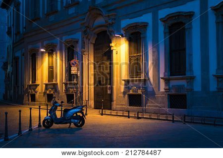 Serene view of a small motorbike parked in an alley in Milan Italy at night under the warm colour of the street light