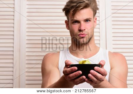 Macho With Serious Face Holds Bowl With Yellow Measure Tape