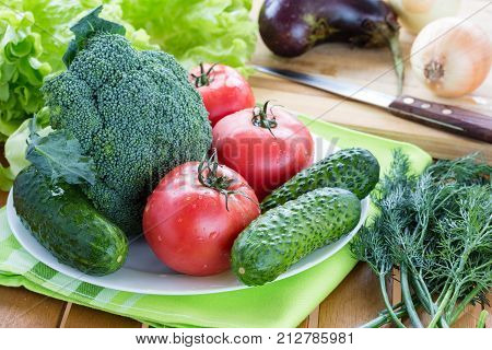 Fresh raw vegetables on white plate on wooden table
