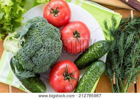 Fresh raw vegetables on white plate on wooden table, top view