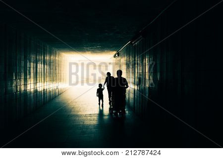Silhouette of happy family with children. Mother and daughter holding hands. Father and baby in stroller going behind. People are walking along the underground tunnel. Light at end of long corridor.