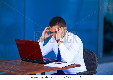 Stressed Overworked Young Business Man With Laptop And Papers Sitting At Table Covering His Face Wit