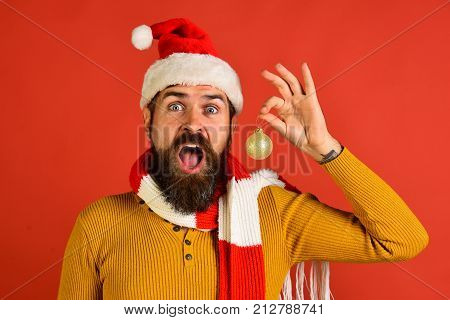 Santa Claus Holds Golden Ball For Fir Tree On Red