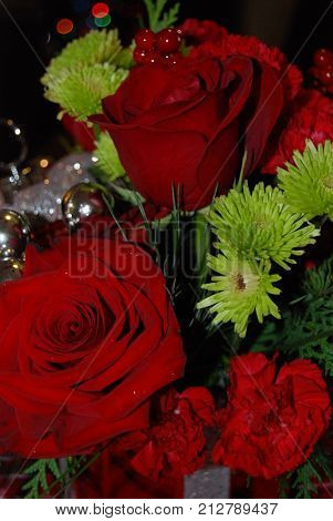 Red and green flower arrangement with ornaments and holly berries.