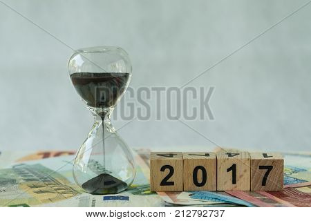 Year end 2017 business time countdown as hourglass or sandglass on pile of Euro banknotes with wooden cube block number 2017.