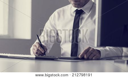 Retro toned image of graphic designer or illustrator using a tablet and stylus pen to do processing and drawing.
