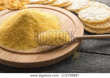 Corn flour and products from it - Wooden spoon full of corn flour on a round wooden board surrounded by products made from it corn flakes and puffed corn cakes on a vintage table in the sunlight.