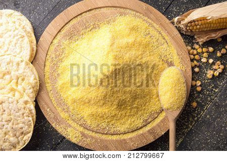 Puffed crispbread and corn flour - Above view with corn flour on a round wooden platter surrounded by corn cakes corn cob and grains on a vintage table.