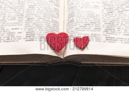 Two hearts on the pages of a book - Close-up image with two red hearts placed on an old open book on a wooden table. A concept for reading learning education or for a love story romantic novel.