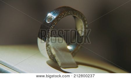Golden finger ring with yellow precious stone. Ring in gold with sapphires browm, wedding ring - jewelery with diamonds and precious gems black background. Silver or white gold ring with yellow gems and diamonds on black glass background