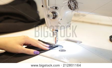 Female tailor stitching material at workplace. Preparing fabric for clothes making. Tailoring, garment industry, fashion designer sketch drawing costume concept and tailor draws sketches. Designer workshop concept.