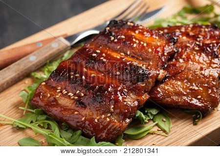 Closeup Of Pork Ribs Grilled With Bbq Sauce And Caramelized In Honey On A Bed Of Arugula. Tasty Snac