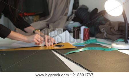 Female tailor stitching material at workplace. Preparing fabric for clothes making. Tailoring, garment industry, fashion designer sketch drawing costume concept and tailor draws sketches. Designer workshop concept. Tailor At Work In Small Business: Fashio