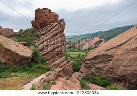 red sandstone rock formations and surrounding mountains of red rocks park in jefferson county colorado