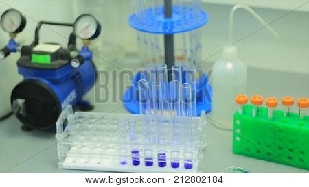 Flask in scientist hand with test tube in rack. Plastic glass tubes for DNA amplification. test tubes with red liquid in laboratory on blue light tint background.