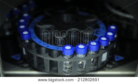 Scientist putting small tube to machine in laboratory. centrifuge laboratory medicine. A centrifuge spins vials of liquid in a laboratory test. Pharmaceutical industry. Medicine manufacturing and lab equipment.