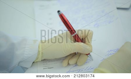 Midsection of doctor writing on paper at clinic. Close up of patient and doctor taking notes. Doctor writing a prescription. Physiotherapist writing on clipboard in clinic. female doctor writing a prescription. a scientist takes notes in a notebook.
