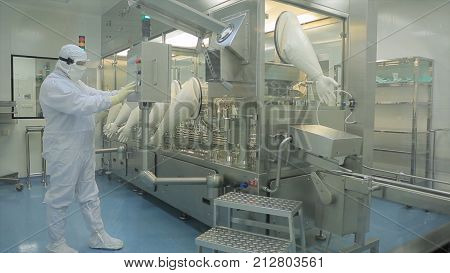 Pharmaceutical industry. Male factory worker inspecting quality of pills packaging in pharmaceutical factory. Automatic tape to create packaging and filling of medicines. control in the factory of medicine