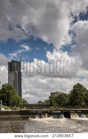 Parramatta Australia - March 24 2017: The circular basin is Parramatta harbor. A dam with open floodgates controls flow in river. Heavy cloudscape. Green belt and office tower under construction.