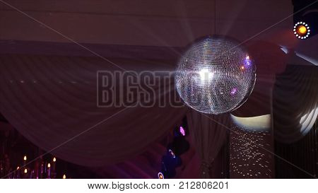 Disco ball with bright rays, night party background. disco ball hanging from the ceiling shines at the party. Disco ball HD