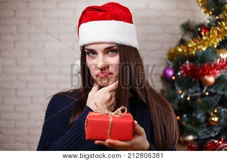 Young Beautiful Woman In Santa Cap Discontented With A Present. New Year, Christmas, Gift, Surprise,