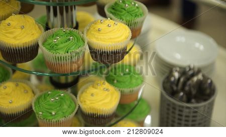 Cupcakes. Amazing chocolate cakes and cupcakes. Chocolate caramel cupcake with nuts and butterscotch syrup. Green and yellow cupcakes. Beautiful cupcakes with colored creams. Wedding cakes. Selective focus. Bokeh And Defocusing Of The LensWedding cakes. C