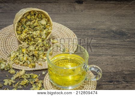 Chrysanthemum tea on wood background Extend the arteries at the heart. Help prevent artery diseases such as hypertension angina.It absorbs.