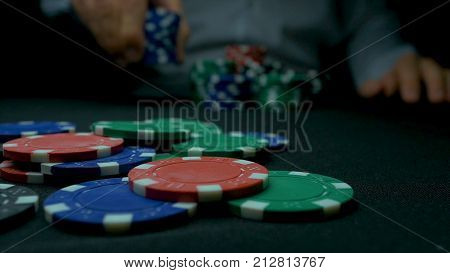 Close-up Of Man Throwing A Poker Chips. Close-up Of Hand With Throwing Gambling Chips On Black Backg