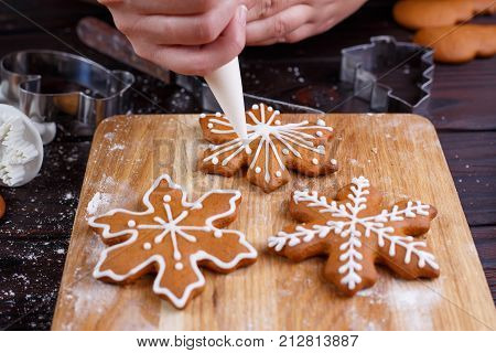 Decorating Christmas Bakery. Woman Hands Decorating Homemade Gingerbread Cookies With Icing, Close U