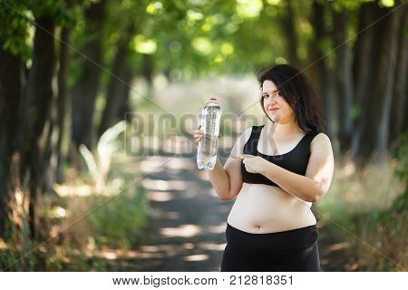 Overweight Fat Woman Pointing On A Bottle Of Water In Her Hand. Young Woman Stay Hydrate For Health.