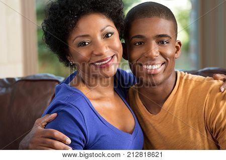 African American mother hugging her adult son.