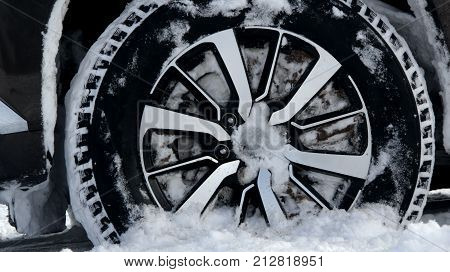 Non studded snow tire on the car wheel in deep snow