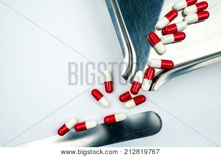 Red white antibiotic capsules pills with shadow on stainless steel drug tray. Drug resistance antibiotic drug use with reasonable health policy and health insurance concept.