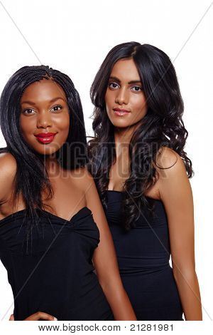 African beautiful woman with long extensions and red lipstick standing next to her Indian friend with long curly hair over white background. Focus on Indian Beauty
