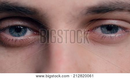 Closeup of young man's blue eyes with problematic skin acne and selective focus. Close-up portrait of a young man with blue eyes - OBS: model use lens contact. Human eye detail. Human eye close-up detail
