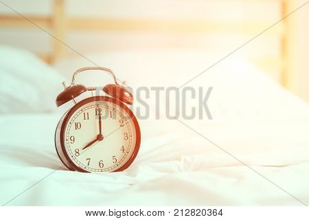 Black alarm clock on bed in room for waking up and ringing bell in the morning every day with sunlight Sleeping snooze concept.