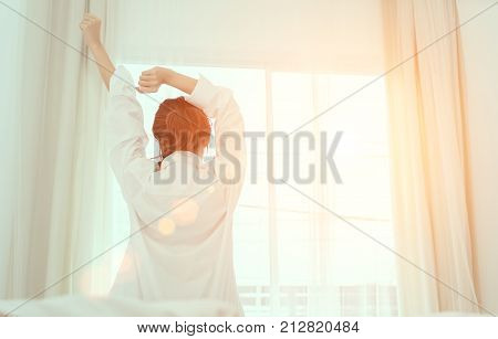 Young woman wake up in the morning and sitting on bed at window door side relaxing in holiday with sunlight back view