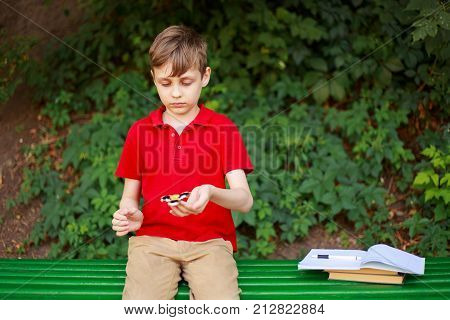 Boy playing with fidget spinner. Education concentration reducing stress people concept