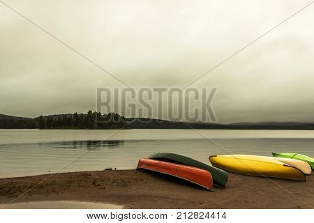 Canada Ontario Lake of two rivers grey morning dark atmosphere Canoe Canoes parked on beach near water in Algonquin National Park