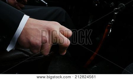 Businessman driving to work, hand shifting the gear stick. Businessman shifts the transmission