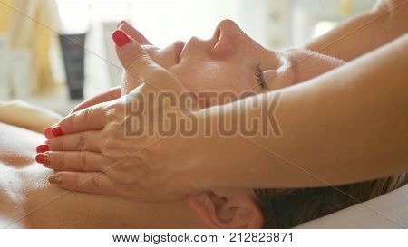 Beautiful young woman relaxing with face massage at luxury spa salon, close-up. Cosmetologist doing facial massage after facial mask procedure.