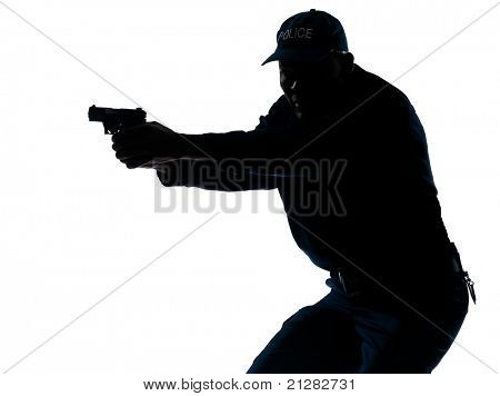Silhouette image of an afro American mature police officer aiming a handgun in studio on white isolated background