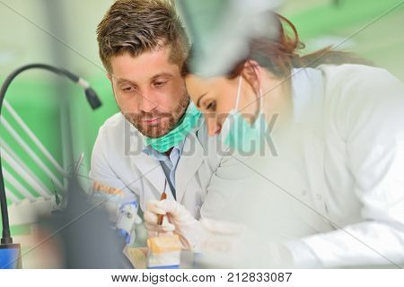 Dental prosthesis, dentures, prosthetics work. Prosthetics hands while working on the denture, false teeth, a study and a table with dental tools.